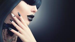 Forme a Dia das Bruxas a menina modelo com penteado preto gótico, composição e tratamento de mãos imagens de stock