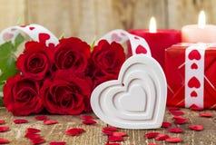Forme du coeur blanc devant le bouquet des roses rouges Images stock