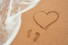 Forme du coeur et empreintes de pas dans le sable sur la plage Photo libre de droits