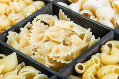 Forme e varietà differenti di pasta in una scatola di legno Immagine Stock