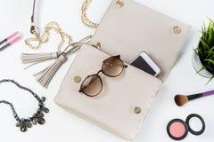 Forme el bolso de la mujer con el teléfono móvil, el maquillaje y accesorios Imagenes de archivo