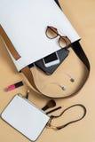 Forme el bolso de la mujer con el teléfono móvil, el maquillaje y accesorios Foto de archivo