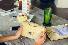 Forme el bolso de lujo del pitón del snakeskin en la tabla de madera en restaurante Isla de Bali Imágenes de archivo libres de regalías