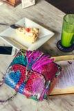 Forme el bolso de lujo del pitón del snakeskin en la tabla de madera en restaurante Isla de Bali Fotografía de archivo libre de regalías