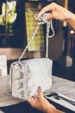 Forme el bolso de lujo del pitón del snakeskin en la tabla de madera en restaurante Isla de Bali Imagen de archivo