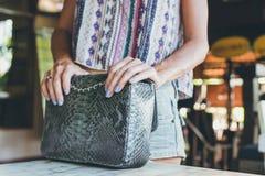 Forme el bolso de lujo del pitón del snakeskin en la tabla de madera en restaurante Isla de Bali Foto de archivo