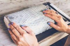 Forme el bolso de lujo del pitón del snakeskin en la tabla de madera en restaurante Isla de Bali Fotos de archivo