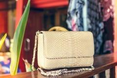 Forme el bolso de lujo del pitón del snakeskin en la tabla de madera en restaurante Isla de Bali Fotografía de archivo