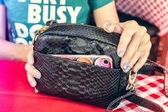 Forme el bolso de lujo del pitón del snakeskin en la tabla de madera en restaurante Isla de Bali Imagen de archivo libre de regalías