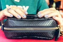Forme el bolso de lujo del pitón del snakeskin en la tabla de madera en restaurante Isla de Bali Foto de archivo libre de regalías
