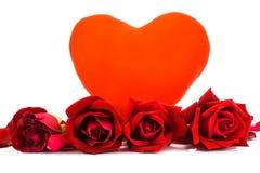 Forme el corazón y las rosas rojas en un fondo blanco Fotos de archivo