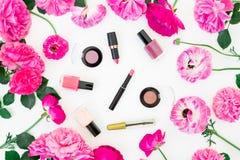 Forme el escritorio del blogger con los cosméticos, lápiz labial, las sombras de ojos y las rosas y ranúnculo rosados en el fondo Imagen de archivo libre de regalías