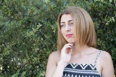 Forme el frente rubio de la mujer de una pared de los verdes Foto de archivo