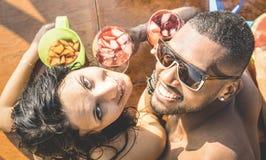 Forme el hombre y a la mujer joven que se divierten en la barra del cóctel Foto de archivo