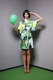 Forme el lanzamiento de una mujer joven en una alineada verde Imagen de archivo