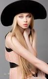 Forme el modelo adolescente en un sombrero grande negro Foto de archivo libre de regalías