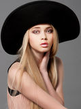 Forme el modelo adolescente en un sombrero grande negro en estudio Fotografía de archivo