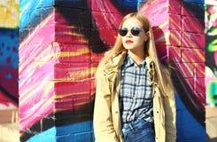 Forme el modelo bastante rubio de la mujer en gafas de sol sobre colorido Imagenes de archivo