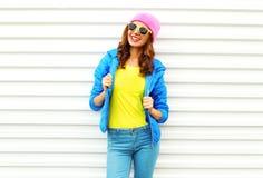 Forme el modelo bastante sonriente de la mujer en la ropa colorida que presenta sobre el fondo blanco las gafas de sol rosadas de Fotografía de archivo libre de regalías