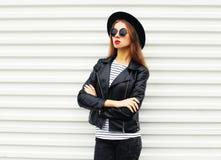 Forme el modelo bonito de la mujer con los brazos cruzados en el estilo negro de la roca que presenta sobre blanco Fotografía de archivo libre de regalías