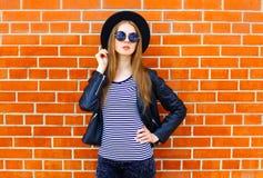 Forme el modelo bonito de la mujer que lleva un estilo negro de la roca que presenta sobre fondo Fotografía de archivo libre de regalías
