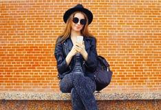Forme el modelo bonito de la mujer usando smartphone en estilo del negro de la roca sobre fondo de los ladrillos Fotografía de archivo libre de regalías