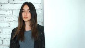 Forme el modelo moreno en la chaqueta de cuero que presenta en el estudio blanco almacen de video