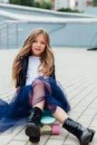 Forme el monopatín del schoolgirlwith del niño en la ciudad en la calle Fotografía de archivo