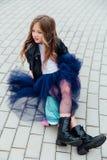 Forme el monopatín del schoolgirlwith del niño en la ciudad en la calle Imagenes de archivo