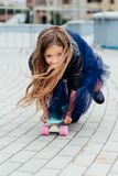 Forme el monopatín del schoolgirlwith del niño en la ciudad en la calle Fotos de archivo