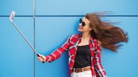 Forme el retrato bastante de la sonrisa y a la mujer en gafas de sol con smartphone contra la pared azul colorida Haga el selfie Imágenes de archivo libres de regalías