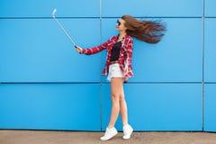 Forme el retrato bastante de la sonrisa y a la mujer en gafas de sol con smartphone contra la pared azul colorida Haga el selfie Imagen de archivo