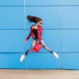 Forme el retrato de la muchacha bastante sonriente y de salto del inconformista en gafas de sol contra la pared azul colorida Pel Fotos de archivo