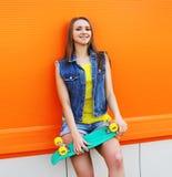 Forme el retrato de la muchacha del inconformista en ropa colorida con el patín Foto de archivo libre de regalías