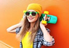 Forme el retrato de la muchacha fresca del inconformista en gafas de sol con el patín Imagen de archivo libre de regalías
