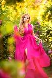 Forme el retrato de la muchacha hermosa joven que presenta contra arbustos de lila en flor fotografía de archivo libre de regalías