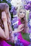 Forme el retrato de la muchacha hermosa joven que presenta contra arbustos de lila en flor foto de archivo