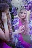 Forme el retrato de la muchacha hermosa joven que presenta contra arbustos de lila en flor fotos de archivo