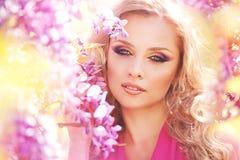 Forme el retrato de la muchacha hermosa joven que presenta contra arbustos de lila en flor imagen de archivo libre de regalías