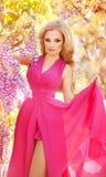 Forme el retrato de la muchacha hermosa joven que presenta contra arbustos de lila en flor fotografía de archivo