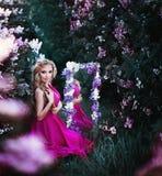 Forme el retrato de la muchacha hermosa joven que presenta contra arbustos de lila en flor imágenes de archivo libres de regalías