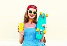 Forme el retrato de la muchacha sonriente feliz con una taza de jugo sobre blanco Foto de archivo