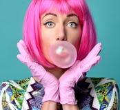 Forme el retrato de la mujer alegre que infla el gumin de la burbuja ho foto de archivo