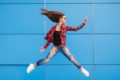 Forme el retrato de la mujer bastante sonriente y de salto en gafas de sol con smartphone contra la pared azul colorida Imagenes de archivo