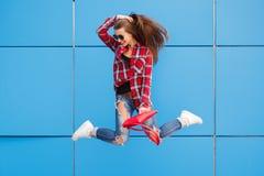 Forme el retrato de la mujer bastante sonriente y de salto en gafas de sol contra la pared azul colorida Pelos del vuelo Fotos de archivo libres de regalías