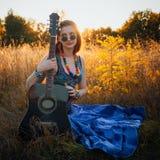 Forme el retrato de la mujer joven del hippie con la guitarra Foto de archivo libre de regalías