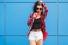 Forme el retrato de la mujer sonriente bonita en gafas de sol con la piruleta contra la pared azul colorida outdoor Foto de archivo libre de regalías
