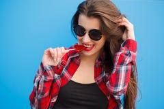 Forme el retrato de la mujer sonriente bonita en gafas de sol con la piruleta contra la pared azul colorida outdoor Foto de archivo