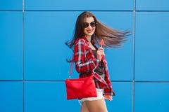Forme el retrato de la mujer sonriente bonita en gafas de sol con la piruleta contra la pared azul colorida outdoor vuelo Fotos de archivo