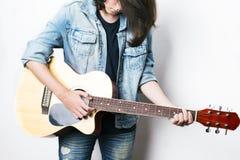 Forme el retrato de un adolescente que toca la guitarra en chaqueta de los vaqueros del estudio que lleva Fotografía de archivo libre de regalías